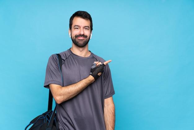 Giovane uomo sportivo con la barba che punta verso il lato per presentare un prodotto