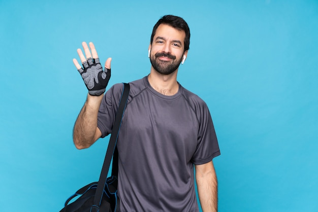 Giovane uomo sportivo con la barba che saluta con la mano con l'espressione felice