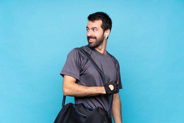 Giovane uomo sportivo con la barba con le braccia incrociate e felice