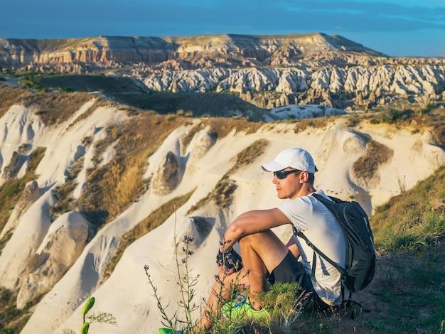 Giovane uomo sportivo in berretto bianco con zaino seduto sul picco di roccia arenaria