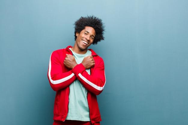Giovane uomo sportivo nero che sorride allegramente e festeggia, con i pugni chiusi e le braccia incrociate, sentendosi felice e positivo contro la parete del grunge
