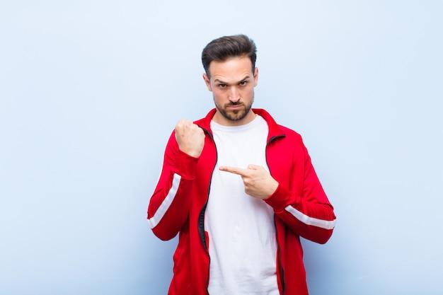 Giovane uomo sportivo o monitor bello dall'aspetto impaziente e arrabbiato, che punta all'orologio, chiedendo puntualità, vuole essere puntuale contro la parete piatta
