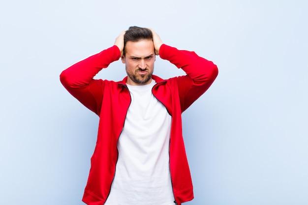 Giovane uomo sportivo o monitor bello sentirsi frustrato e infastidito, malato e stanco di fallire, stufo di compiti noiosi e noiosi contro la parete verde