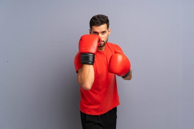 Giovane uomo sportivo sul muro grigio con guantoni da boxe
