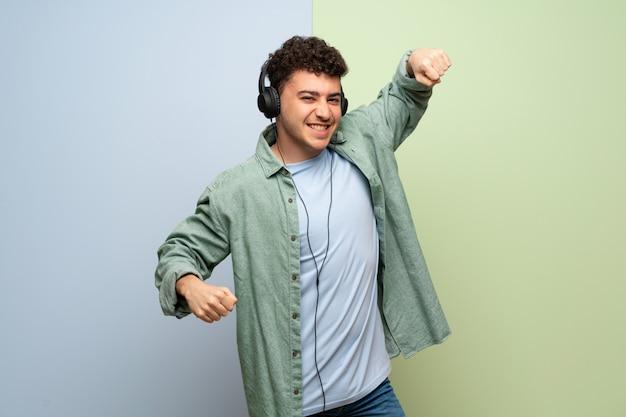 Giovane uomo su blu e verde ascoltando musica con le cuffie e ballare