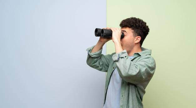 Giovane uomo su sfondo blu e verde e guardando in lontananza con il binocolo