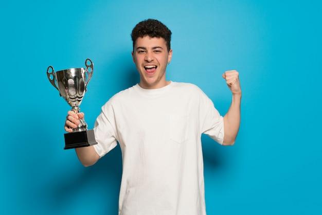 Giovane uomo su sfondo blu in possesso di un trofeo