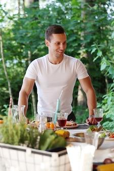 Giovane uomo su una salsiccia e mais alla griglia