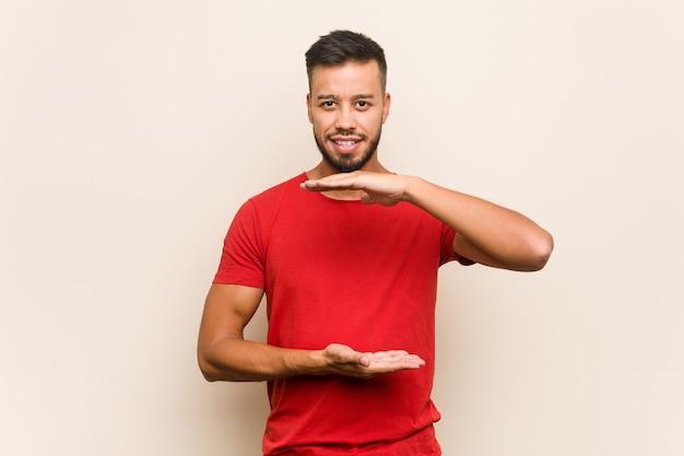 Giovane uomo sud-asiatico che tiene qualcosa con entrambe le mani, presentazione del prodotto.