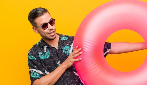 Giovane uomo sud-asiatico che tiene un anello galleggiante