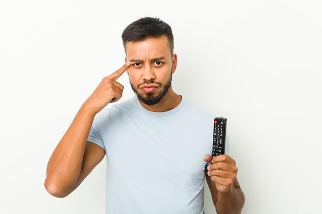Giovane uomo sud-asiatico che tiene un controller tv che mostra un gesto di delusione con l'indice.