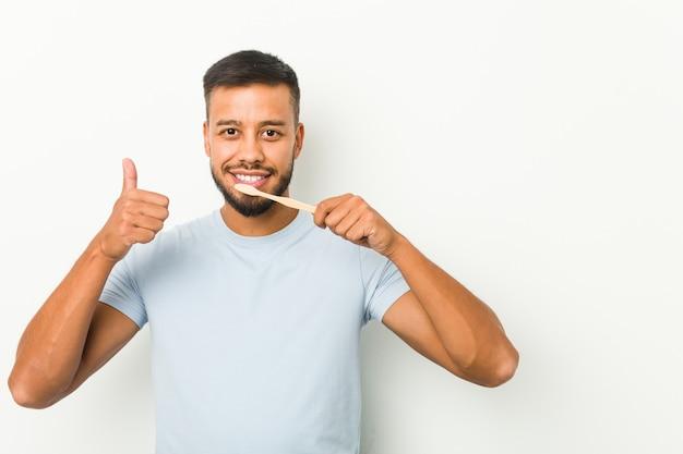 Giovane uomo sud-asiatico che tiene uno spazzolino da denti che sorride e che alza pollice in su