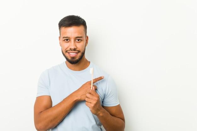 Giovane uomo sud-asiatico che tiene uno spazzolino da denti che sorride e che indica da parte, mostrando qualcosa nello spazio.