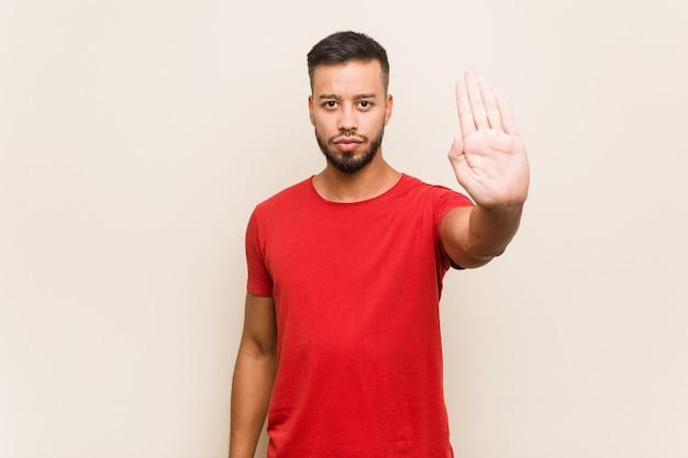 Giovane uomo sud-asiatico in piedi con la mano tesa che mostra il segnale di stop, impedendoti.