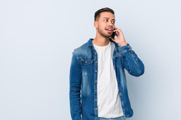 Giovane uomo sud-asiatico in possesso di un telefono