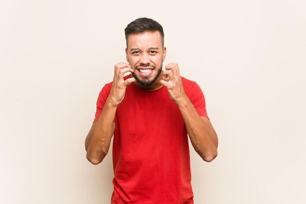 Giovane uomo sud-asiatico sconvolto urlando con le mani tese.