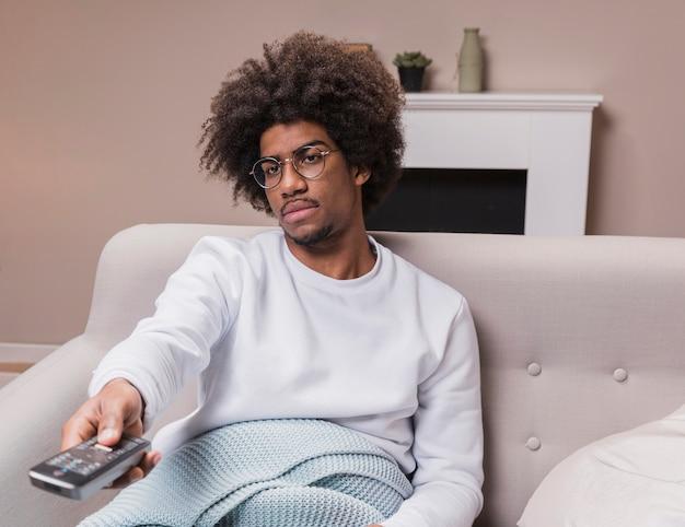 Giovane uomo sul divano con telecomando