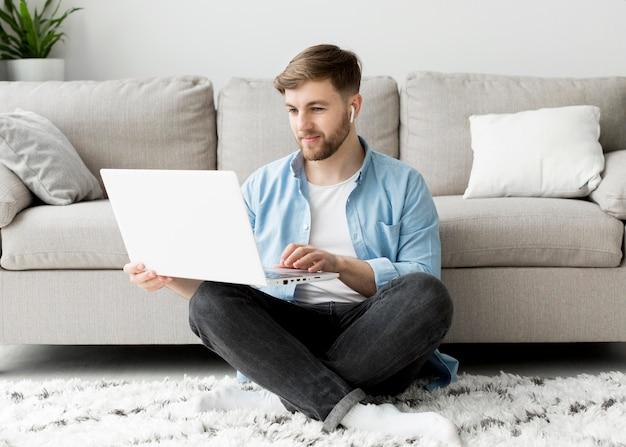 Giovane uomo sul pavimento con il portatile