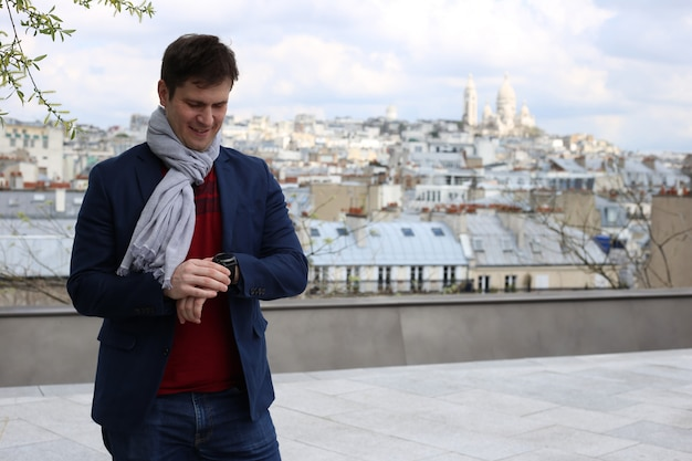 Giovane uomo sul tetto a parigi guarda l'orologio da polso vicino alla basilica del sacro cuore