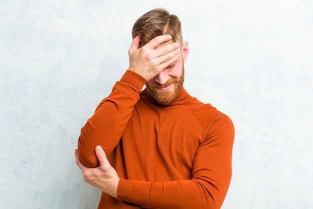 Giovane uomo testa rossa che indossa il collo di tartaruga cercando stressato, vergogna o sconvolto, con un mal di testa, che copre il viso con la mano contro il muro di cemento