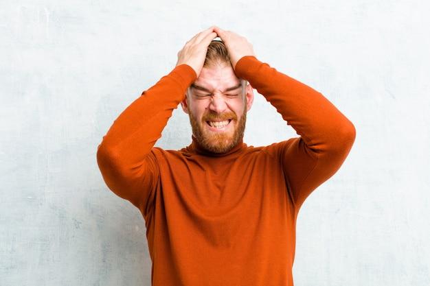 Giovane uomo testa rossa che indossa il collo di tartaruga sensazione stressato e ansioso, depresso e frustrato con un mal di testa, alzando entrambe le mani a testa contro il muro di cemento