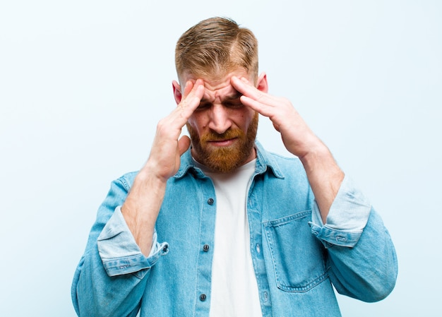 Giovane uomo testa rossa che sembra stressato e frustrato, che lavora sotto pressione con un mal di testa e travagliato da problemi contro la morbida parete blu