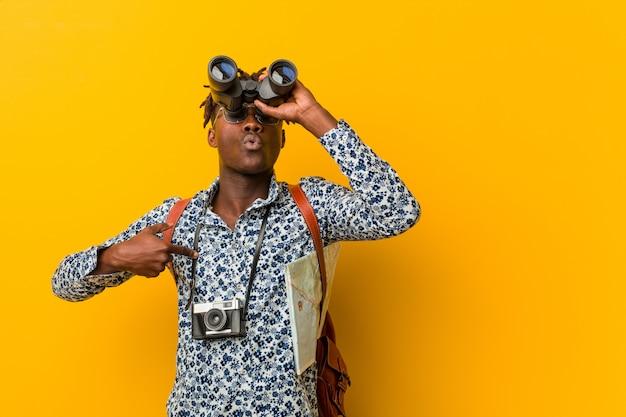 Giovane uomo turistico africano che sta contro un fondo giallo che tiene un binocolo