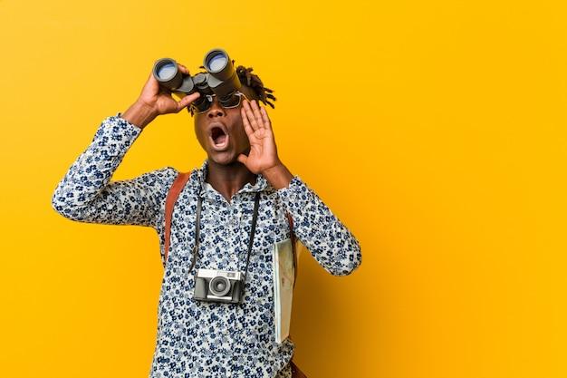 Giovane uomo turistico africano che sta contro una parete gialla che tiene un binocolo