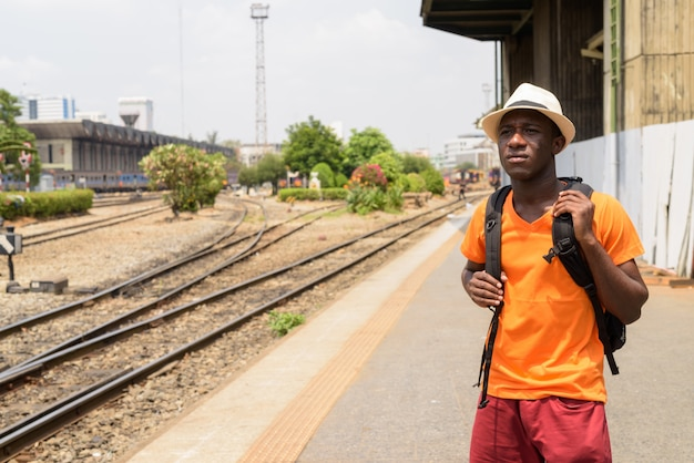 Giovane uomo turistico che pensa mentre aspettando il treno nelle vie contro la vista delle piste del treno a bangkok tailandia
