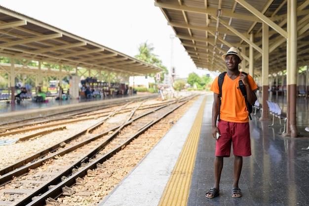 Giovane uomo turistico felice che sorride e che pensa mentre aspettando il treno alla stazione ferroviaria contro la vista delle piste del treno a bangkok tailandia.