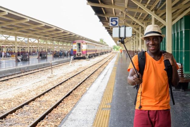 Giovane uomo turistico felice che sorride e che prende l'immagine del selfie con il telefono cellulare sul bastone del selfie alla stazione ferroviaria contro la vista delle piste del treno a bangkok tailandia.