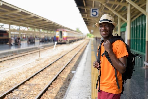 Giovane uomo turistico felice che sorride mentre aspettando il treno alla stazione ferroviaria contro la vista delle piste del treno a bangkok tailandia