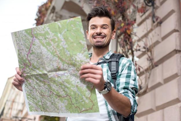 Giovane uomo turistico sorridente con una mappa della città.