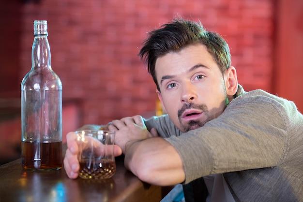 Giovane uomo ubriaco che beve alcool nella barra.