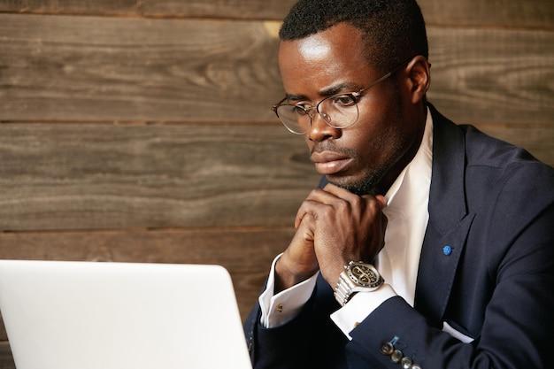 Giovane uomo vestito in abito formale utilizzando laptop