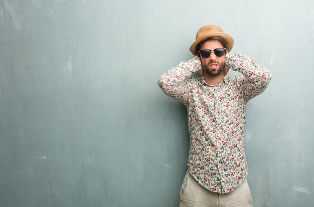 Giovane uomo viaggiatore che indossa una camicia colorata che copre le orecchie con le mani