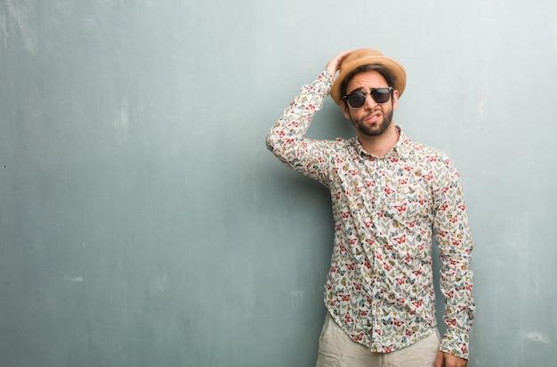 Giovane uomo viaggiatore che indossa una maglietta colorata preoccupata e sopraffatta, smemorata