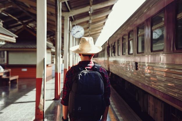 Giovane uomo viaggiatore stand sulla stazione ferroviaria