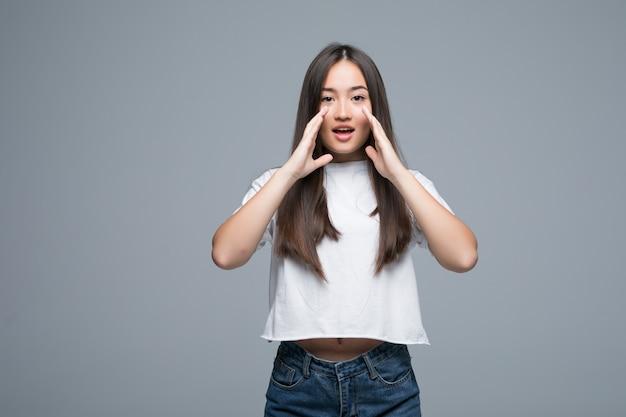 Giovane urlo asiatico rumoroso isolato su sfondo grigio