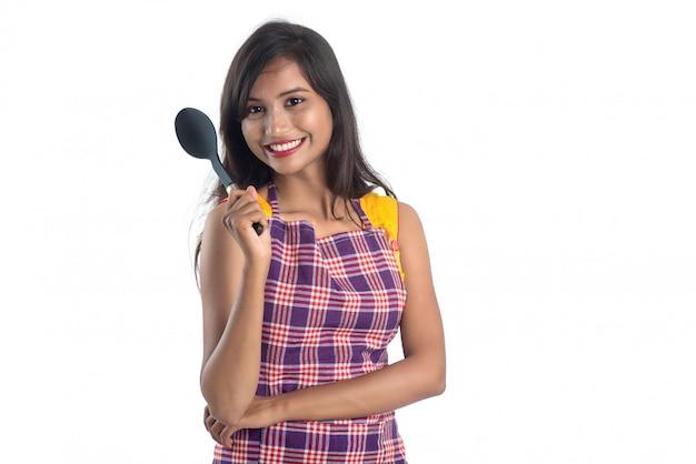 Giovane utensile da cucina indiano della tenuta della donna (cucchiaio, graffetta, siviera e pentola, ecc.) su bianco