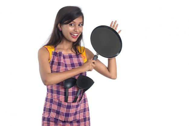 Giovane utensile da cucina indiano della tenuta della donna (cucchiaio, graffetta, siviera e pentola, ecc.) su un bianco
