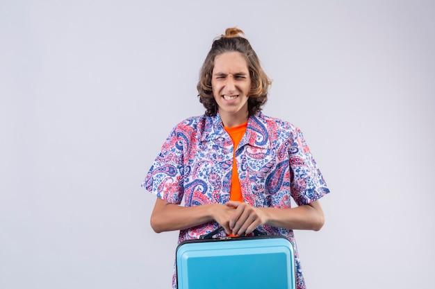 Giovane valigia infastidita del viaggiatore del tipo bello infastidita e frustrata con qualcosa che tiene gli occhi chiusi in piedi