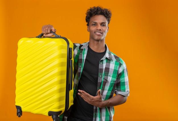 Giovane viaggiatore afroamericano che tiene la valigia che presenta con il braccio della sua mano che guarda l'obbiettivo sorridente fiducioso in piedi positivo e felice su sfondo arancione