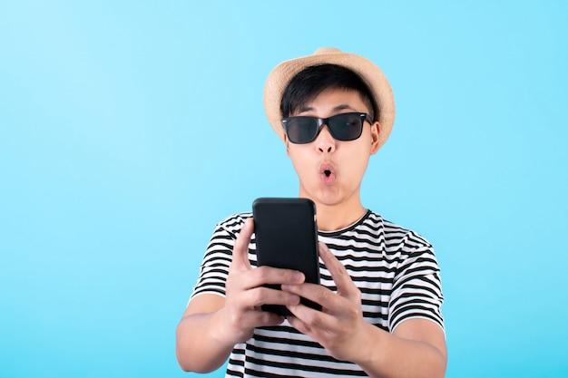 Giovane viaggiatore asiatico è scioccato da uno smartphone su un blu