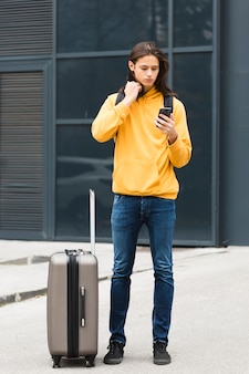 Giovane viaggiatore bello che controlla il suo telefono