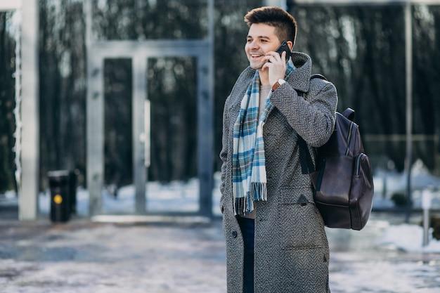 Giovane viaggiatore bello dell'uomo che per mezzo del telefono fuori