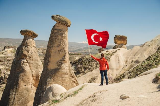 Giovane viaggiatore con bandiera turca nel paesaggio desertico della cappadocia