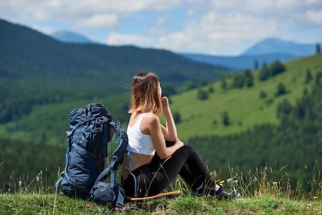Giovane viaggiatore con zaino e sacco a pelo femminile con lo zaino blu che si siede sulla cima di una collina