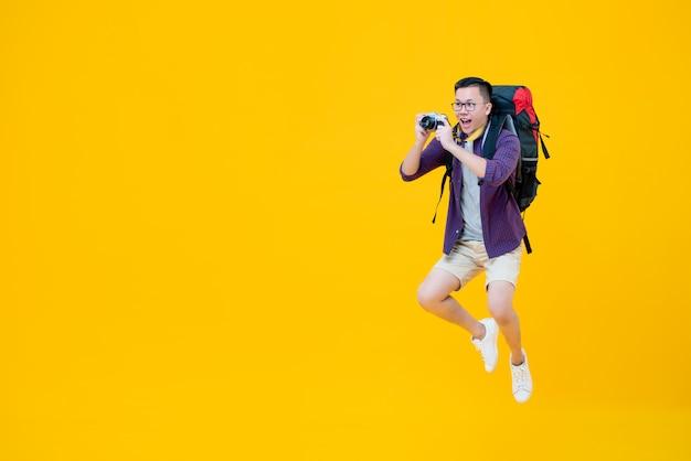 Giovane viaggiatore con zaino e sacco a pelo maschio asiatico felice che prende foto mentre saltando accanto allo spazio della copia