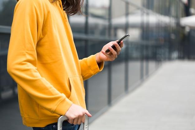 Giovane viaggiatore del primo piano che controlla il suo telefono